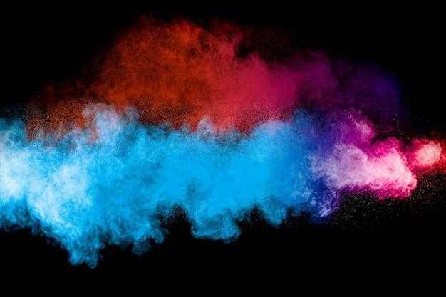 Uruchomiono wielokolorowy proszek na czarnym tle. eksplozja proszku w kolorze. kolorowe rozpryski pyłu.