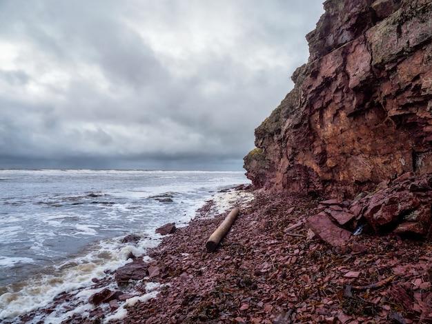 Urwisko nad morzem z wąską linią brzegową. duży kłód wyrzucony na plażę. fale z białą pianą toczą się po skalistym brzegu. wybrzeże terskie, statek cape ship na półwysep kolski.