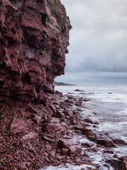 Urwisko nad morzem z wąską linią brzegową. fale z białą pianą toczą się po skalistym brzegu. wybrzeże terskie, statek cape ship na półwysep kolski.