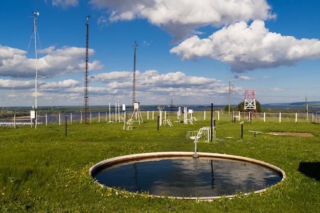 Urządzenia do pomiaru prędkości wiatru, opadów w stacji pogodowej w letni dzień. stacja pogodowa znajduje się na wysokim wzgórzu