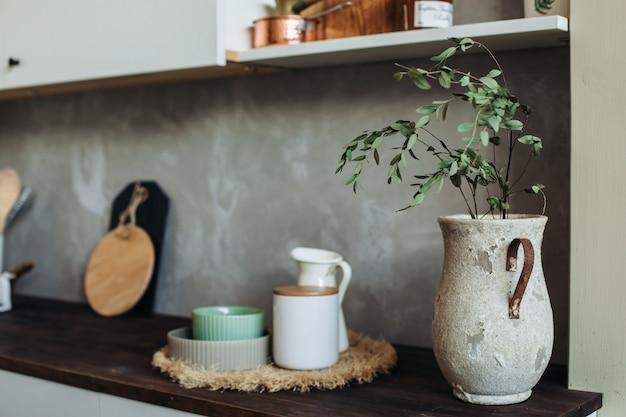 Urządzenia kuchenne metalowe i drewniane. widelec, łyżka i łopatka na drewnianym blacie, przy szarej teksturowanej ścianie. martwa kuchnia do gotowania. kopia miejsca.