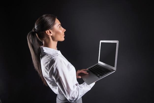 Urzadzenie cyfrowe. wesoła pozytywna ładna bizneswoman stojąca na czarnym tle i trzymając laptopa, patrząc na to