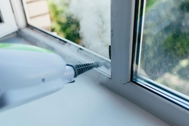 Urządzenie czyszczące wdmuchuje strumień pary do ramy okiennej, aby usunąć brud.