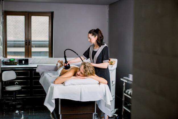 Urządzenie do masażu próżniowego. antycellulitowy zabieg korygujący ciało. aparat do utraty wagi. młoda blond kobieta i kobieta lekarz w nowoczesnym salonie spa i pielęgnacji ciała.
