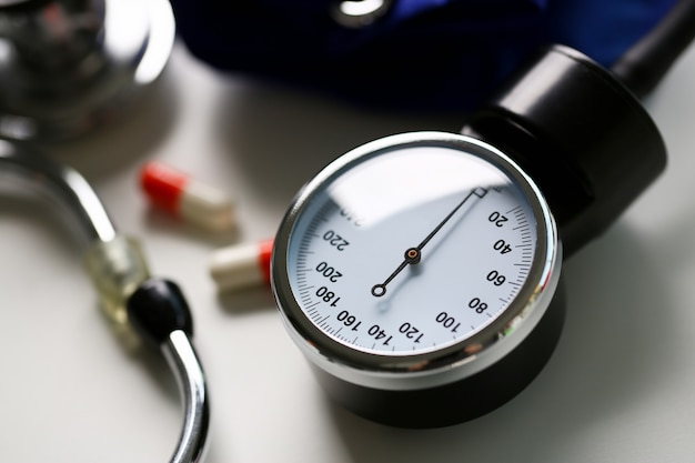Urządzenie do pomiaru ciśnienia krwi w gabinecie lekarskim na stole. zapobieganie chorobom naczyniowym związanym z nieaktywnym trybem życia zmienia zachowania żywieniowe.