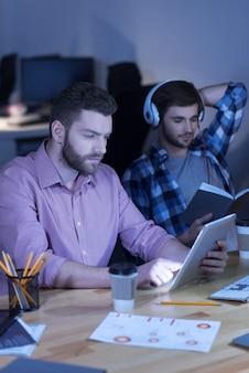 Urządzenie elektroniczne. przemyślany miły brodacz siedzi przy stole i podczas pracy patrzy na ekran tabletu