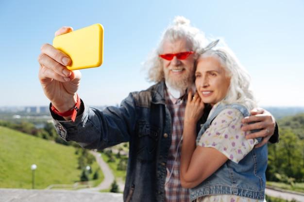 Urządzenie elektroniczne. selektywne skupienie się na nowoczesnym smartfonie używanym przez pozytywną starszą parę podczas robienia selfie