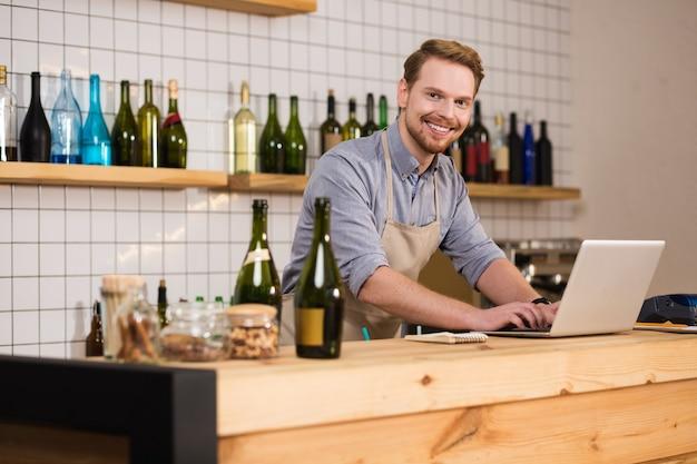 Urządzenie technologiczne. wesoły pozytywny przystojny mężczyzna stojący przed laptopem i patrząc na ciebie podczas używania go do pracy
