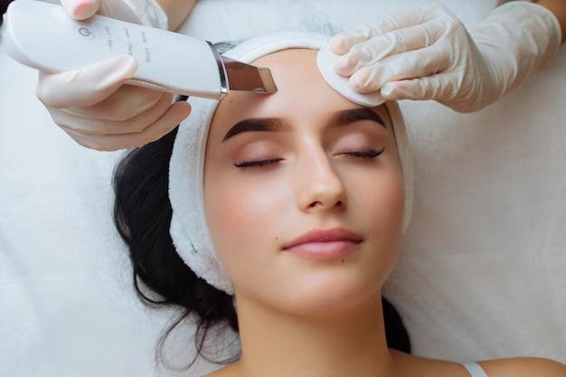 Urządzenie ultradźwiękowe w rękach profesjonalnej afro kosmetyczki