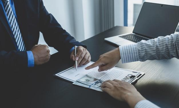 Urzędnicy państwowi podpisują ręcznie umowę na otrzymanie pieniędzy z łapówki od biznesmena