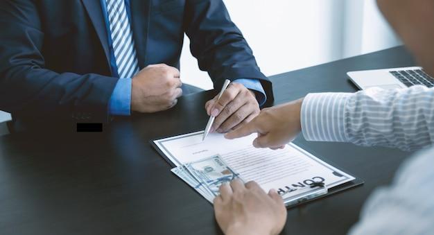 Urzędnicy państwowi podpisują umowę na otrzymanie pieniędzy z łapówki od biznesmena koncepcja przeciwdziałania łapówkarstwu