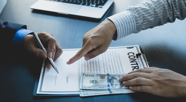 Urzędnicy państwowi wręczają do podpisania kontrakt na otrzymanie pieniędzy z łapówki od biznesmena