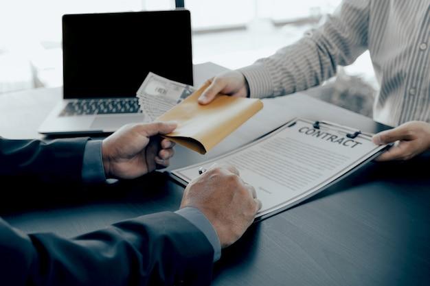 Urzędnicy państwowi wręczają do podpisania umowę na otrzymanie pieniędzy z łapówki od biznesmena
