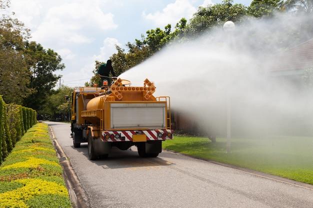Urzędnicy rozpylają wodę z atomizera, na dużej ciężarówce na wolnym powietrzu.