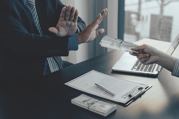 Urzędnicy rządowi podnoszą rękę, odmawiając pieniędzy, by wziąć łapówkę od biznesmena