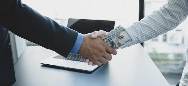 Urzędnicy rządowi wręczają łapówki od biznesmena, ściskając dłonie
