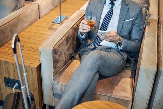 Urzędnik biznesowy wysyła sms-a przez telefon, trzymając drinka