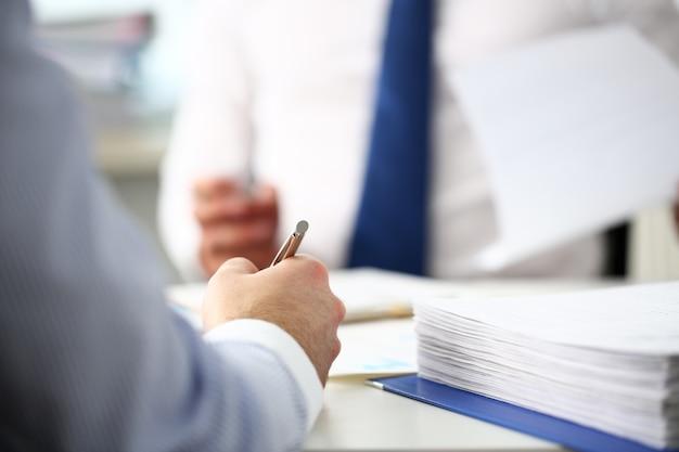 Urzędnik człowiek w biurze pracy ze srebrnym piórem w ręku
