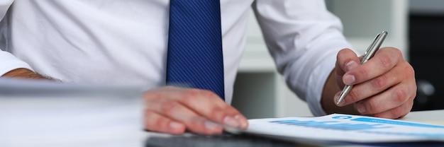 Urzędnika mężczyzna przy biurowym miejscem pracy z srebnym piórem w rękach robi papierkowej roboty zbliżeniu. pracownicy dress code pracownik oferty pracy wizyta u klienta badanie zawód szef rynku pomysł trenera trenera