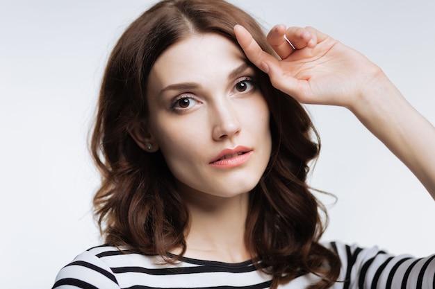 Urzekające piękno. całkiem kasztanowowłosa młoda kobieta w pasiastym swetrze, pozowanie na szarym tle i patrząc w kamerę