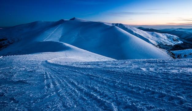 Urzekający piękny widok na góry i wzgórza w zaśnieżonej dolinie późnym wieczorem