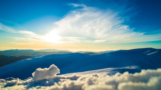 Urzekający widok na majestatyczne zaspy śnieżne położone w górach w słoneczny bezchmurny zimowy dzień