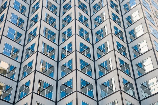 Urzekający wzór okien. nowoczesna architektura miasta wieżowiec. nowoczesna architektura budynku. niebo odbija się w lustrzanych szybach. koncepcja architektury. centrum biznesowe. abstrakcyjne tło.