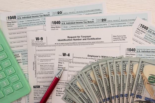 Us indywidualny formularz 1040 z kalkulatorem banknotów dolarowych i dokumentacją pióra. koncepcja rachunkowości
