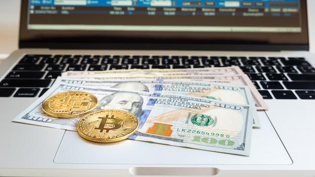 Usa banknot z bitcoin i dane na laptopie dla biznesowego tła