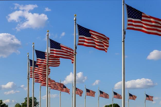Usa flaga macha nad niebieskim niebem blisko waszyngtońskiego zabytku, washington dc
