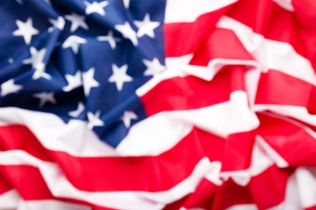 Usa flaga tło zamazany dla projekta. amerykańska flaga narodowa jako symbol demokracji, patrioty, amerykańskiego dnia pamięci lub 4 lipca. tekstura zbliżenie flaga stanów zjednoczonych ameryki lub flaga usa