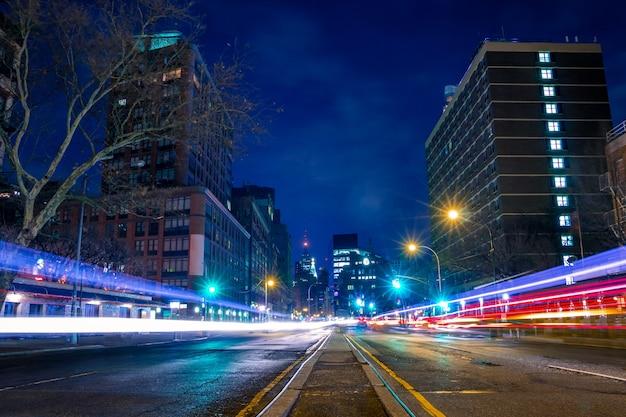 Usa, nowy jork. nocna ulica manhattanu i ślady z reflektorów samochodowych