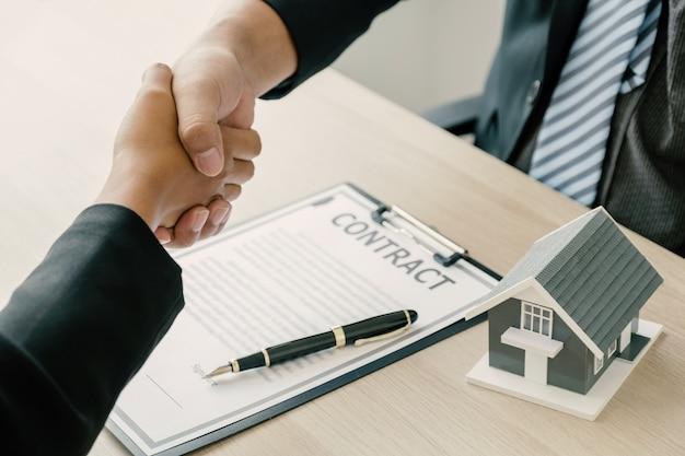 Uścisk dłoni agent nieruchomości wyjaśnia umowę biznesową kupującemu