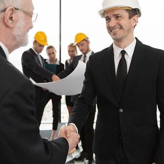 Uścisk dłoni architekta i inwestora, zespół biznesowy z planem na tle