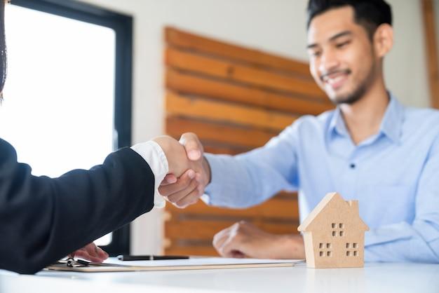 Uścisk dłoni azjatyckiego biznesmena z agentem nieruchomości po zawarciu umowy o kredyt mieszkaniowy