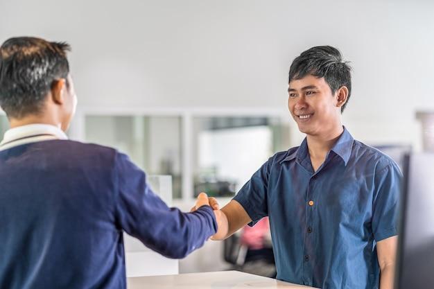 Uścisk dłoni azjatyckiego mechanika z klientem i liderem w centrum serwisowym