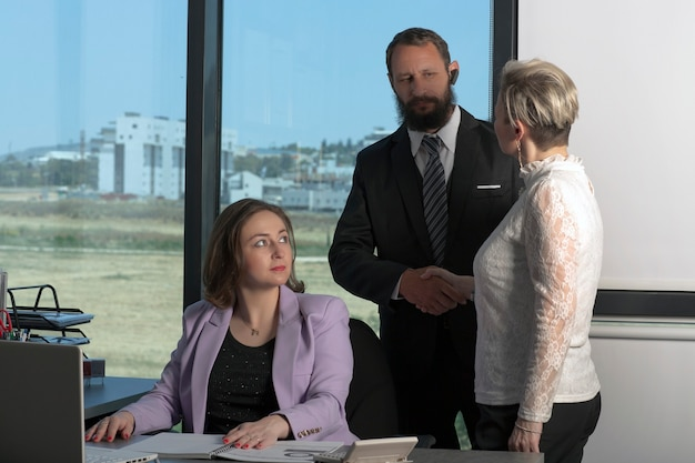 Uścisk dłoni: doradca wita się ze swoją klientką. mężczyzna i kobieta, ściskając ręce, aby przywitać się w biurze. osoby zajmujące się umowami. zespół młodych projektantów dyskutujących o nowym projekcie w nowoczesnym biurze