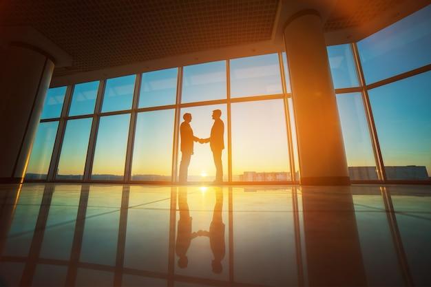 Uścisk dłoni dwóch biznesmenów w biurze na jasnym tle słońca