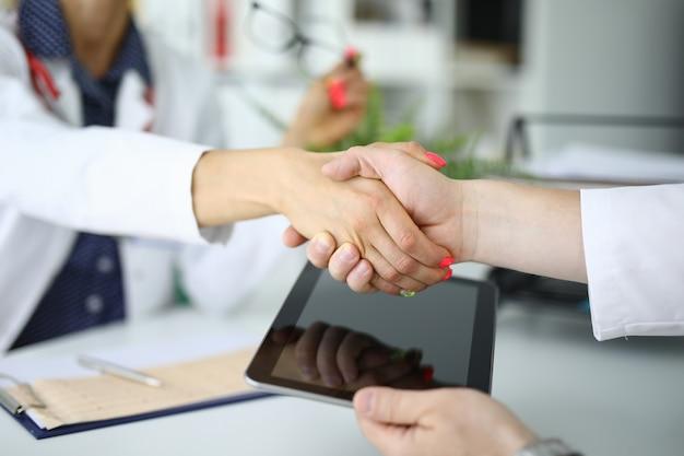 Uścisk dłoni dwóch lekarzy, jeden trzyma tabletkę. koncepcja umów ubezpieczenia medycznego