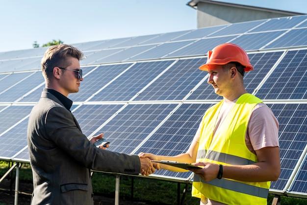 Uścisk dłoni dwóch mężczyzn po zawarciu umowy na tle paneli słonecznych.