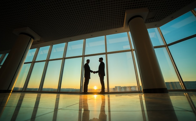 Uścisk dłoni dwóch mężczyzn w biurze na tle zachodu słońca