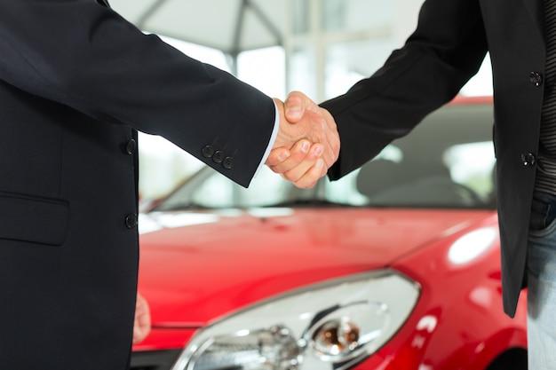 Uścisk dłoni dwóch mężczyzn w garniturach z czerwonym samochodem