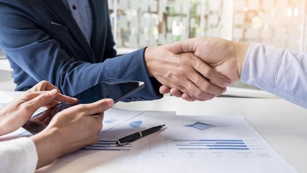 Uścisk dłoni dwóch mężczyzn wykazujących zgodę na podpisanie umowy lub umowy między ich firmami, firmami, przedsiębiorstwami