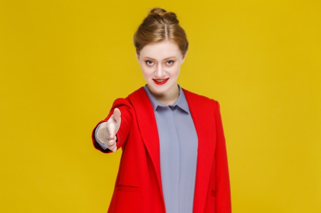 Uścisk dłoni imbir czerwona głowa biznes kobieta w czerwonym garniturze pokazując znak uścisku dłoni