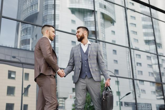 Uścisk dłoni ludzi biznesu na zewnątrz nowoczesny biurowiec