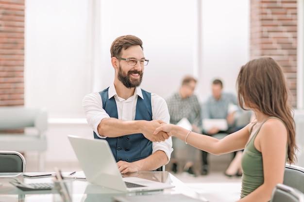 Uścisk dłoni managera i klienta przy biurku.