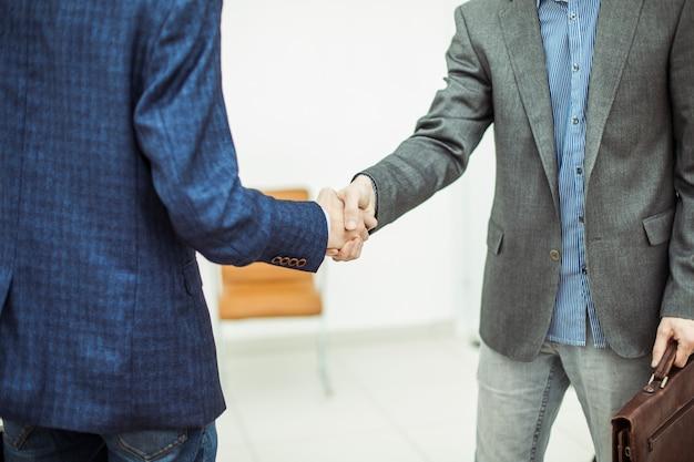 Uścisk dłoni między klientem a menadżerem na tle biura