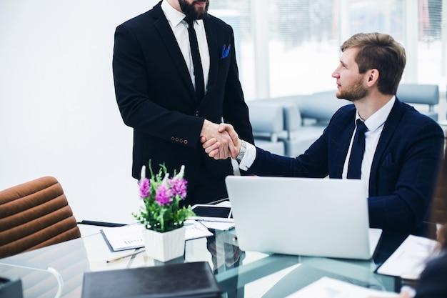 Uścisk dłoni między kolegami w miejscu pracy w nowoczesnym biurze. zdjęcie ma puste miejsce na tekst