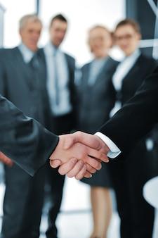 Uścisk dłoni odizolowywający na biznesowym tle