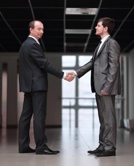 Uścisk dłoni partnerów biznesowych na korytarzu biura